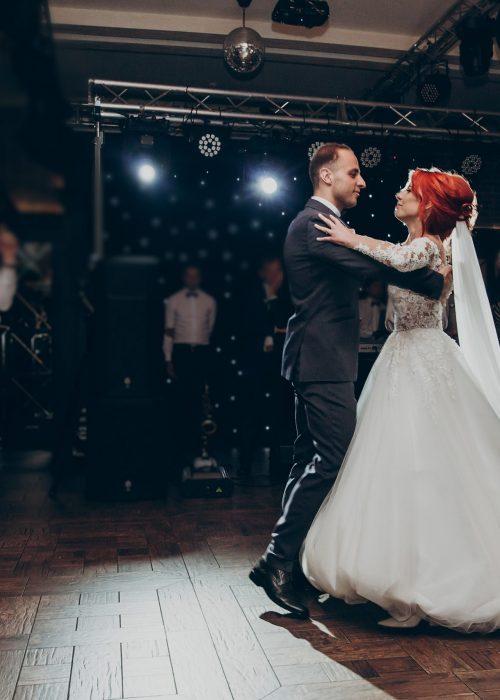 happy bride and stylish groom dancing at wedding reception.